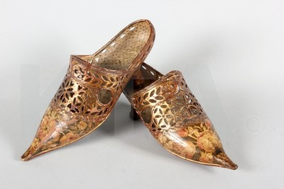 A fine and rare pair of gilded and painted carved wood ladies shoes, Italian, Dutch or French, second half 17th century, of pierced and carved gesso and lacquered wood, the exaggerated pointed toes painted with tulips and dog roses, the upper with lace-effect piercings with faux latchets and eyelets for threading ribbons, foliate medallions and hearts, curved and gilded low set heels with faux stitch marks up the centre back and also to the sides of the upper, the interiors painted with faux erm