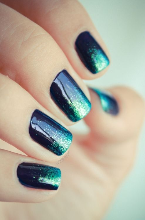 Dark Blue space nails with teal glitter painted onto tips.