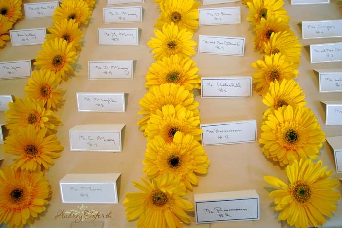 Yellow daises accent a place card table.