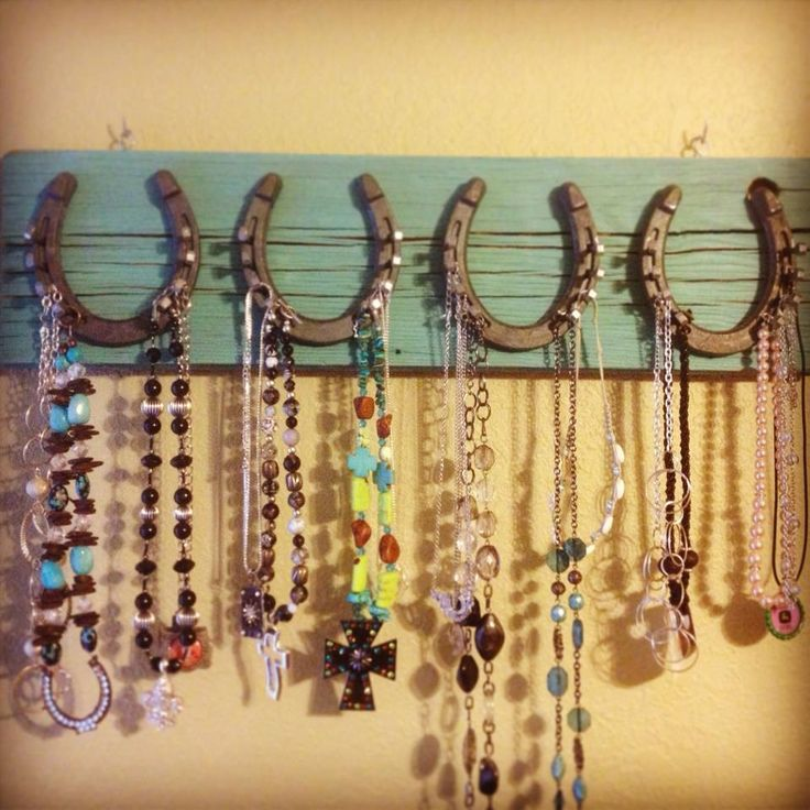 horseshoes mounted on a board with nails added to hold necklaces & bracelets