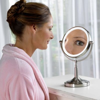 """Dual-sided 7"""" lighted vanity mirror rotates from standard viewing to 5x magnification, ideal for tweezing or putting on makeup. Pivot the double- distortion-free glass vanity mirror to the exact position you need, whether you're sitting at your dresser table or standing at the bathroom counter."""