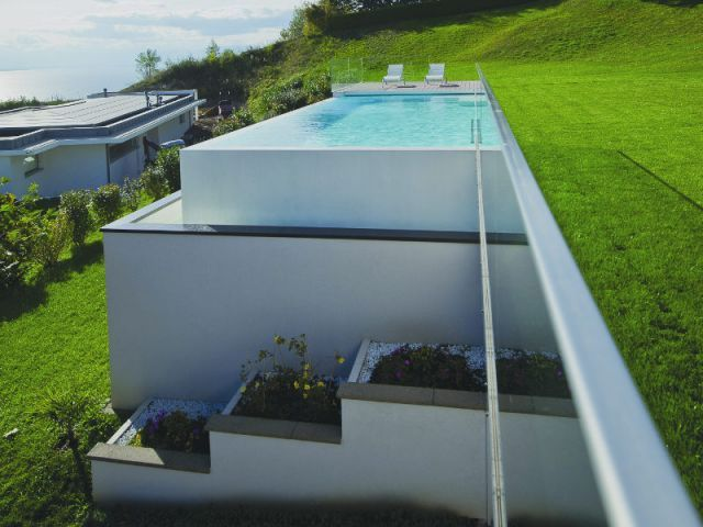 Piscine à débordement avec terrasse en bois et béton