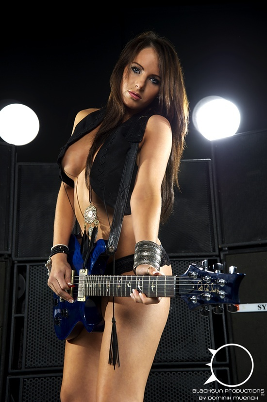 Busty babe playing guitar
