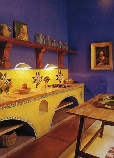 Primary blue walls serve as backdrop for bright yellow cabinets with tile detail
