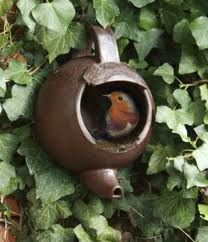<3  Old teapot turned spout down (which will make sure any water drains) in the garden for bird nests...clever art in the garden!