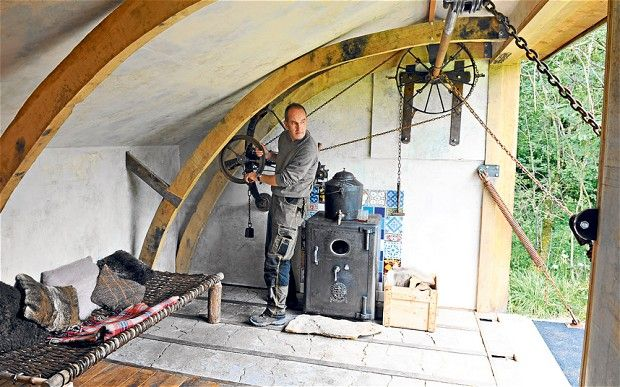 Kevin McCloud lowers the wall of his eco-cabin with winding gear made from a horse trailer and car parts