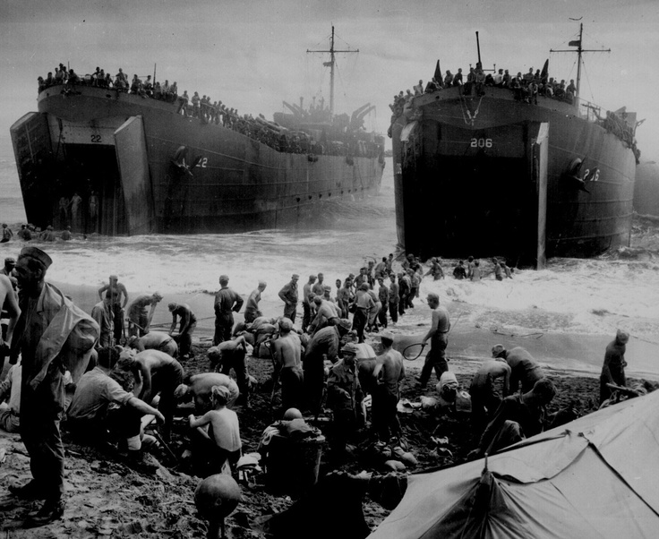 Men built sandbag piers at a Leyte beach while two US Coast Guard-manned LSTs opened their cargo bay doors, circa late 1944