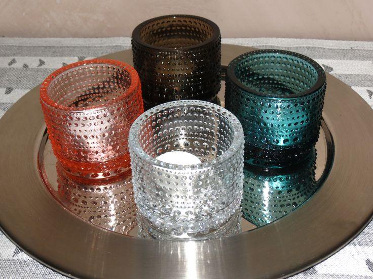 Portacandele Kastehelmi in 4 colori su un piatto di acciaio di Sarpaneva (design per Iittala del 1970). Sotto un runner di Lapuan Kankurit: Koivu (betulla).