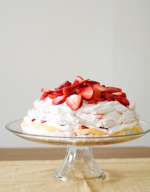 Pavlova cake filled with lemon curd, cream and fresh strawberries