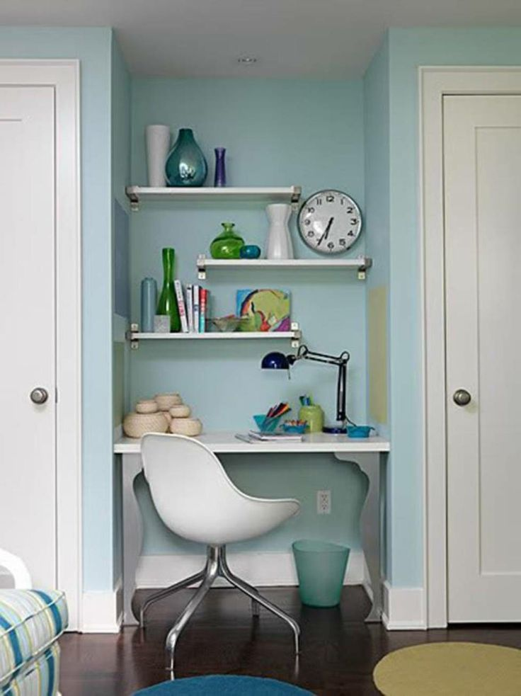 Modern small home office with open shelving and white plastic chair with nickel legs