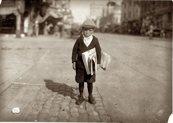 """Looks so innocent. Shortchanger: A 6-year-old newsie who tried to """"short change"""" me. Los Angeles, California. May 1915. View full size. Photograph by Lewis Wickes Hine."""