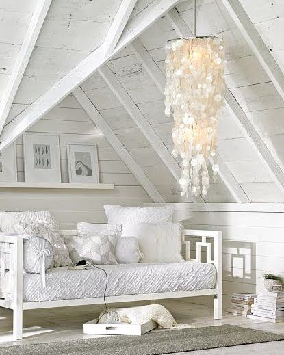 Beautiful white room with hanging iridescent chandelier shell chandelier.