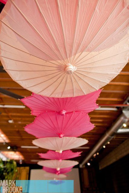 Parasols hang from the ceiling for the wedding reception. Also works on walls?