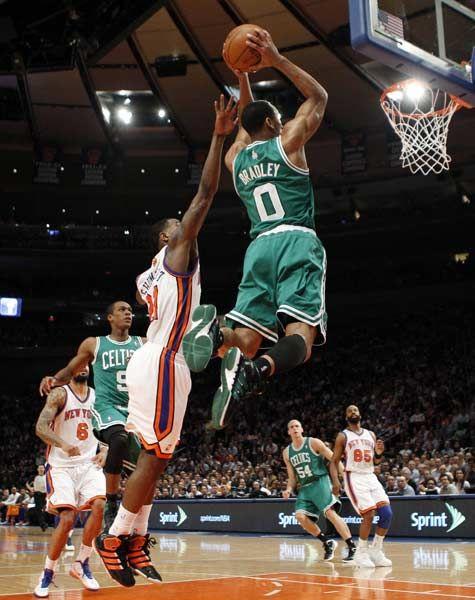 Boston Celtics' Avery Bradley (R) leaps for a dunk past New York ...
