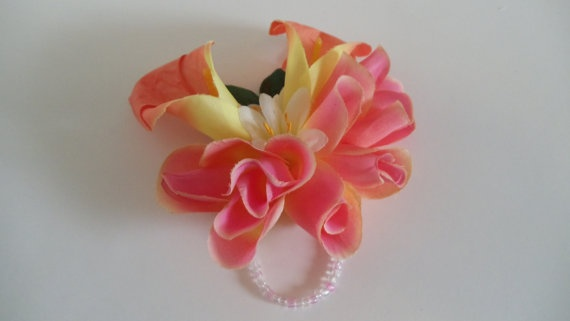 Bright silk roses and calla lilies with two little spring white flowers in a beautiful arrangement. The roses and lilies are in beautiful colors of yellow, coral, and pink. The bracelet has iridescent white and pink glass beads and is made of stretchy string to fit most wrists.    The great thing about this corsage is that, unlike ones made with real flowers, this will keep forever!    $25 at www.deonanddionfashions.etsy.com