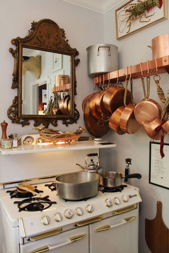 tiny kitchen with mirror above stove and collection of copper pots