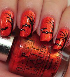 Festive Halloween nail art with spooky bats on a shimmering orange base. by Kelly Ruiz.