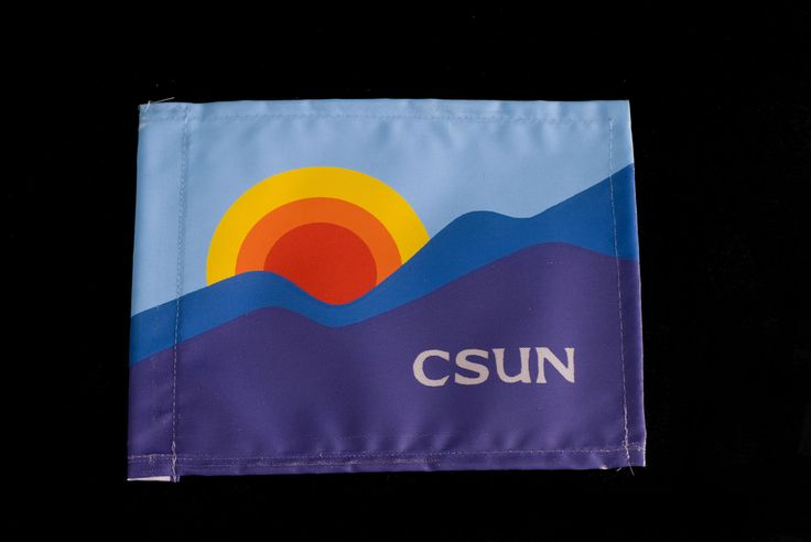 The CSUN rainbow flag was designed by  alumnus Michael O'Meara (Art '78) winner of the 20th Anniversary Flag Design Contest in 1978. According to the artist, the flag incorporated two characteristics associated with the San Fernando Valley, the surrounding mountains and the sunshine.This flag was found in the University's 25th Anniversary time capsule, opened as part of the University's 50th Anniversary celebrations. CSUN University Digital Archives.