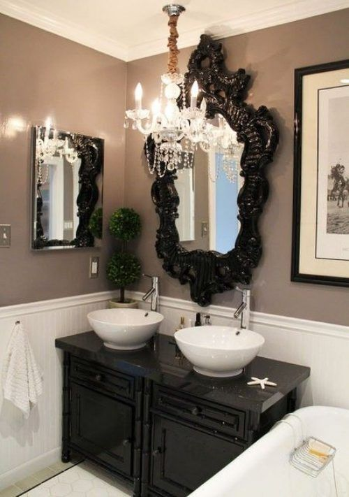 Mauve walls, ornate black mirror, chandelier, white wall paneling, black frames