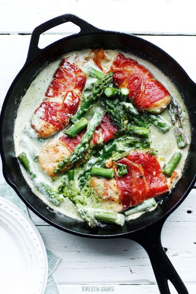 prosciutto wrapped chicken fillet with asparagus and pesto sauce.