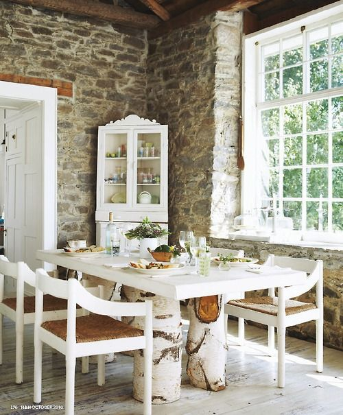 Rustic dining room w/ stone walls and tree stump table