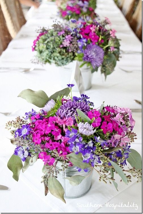 purple flowers in galvanized buckets on table