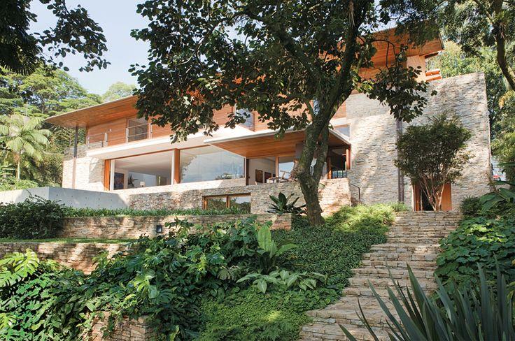 de pedra, madeira e vidro se integra ao jardim em São Paulo  Casa