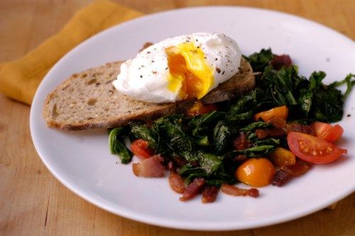 Poached egg over wilted greens with bacon and tomatoes