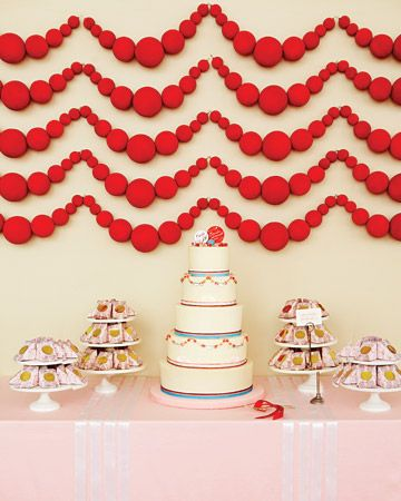 The bride crafted these crimson garlands in the background by spray painting foam balls and stringing them on fishing line
