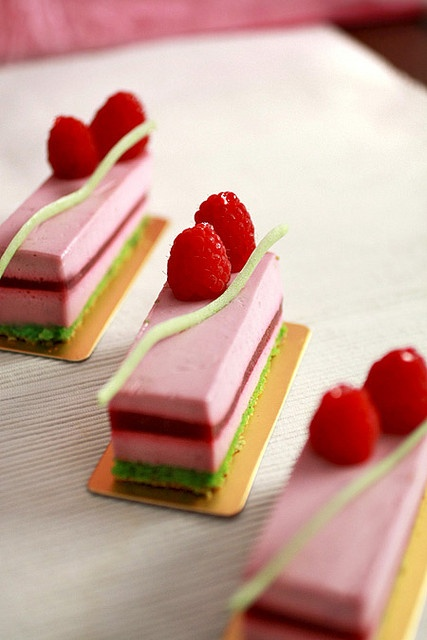 amelie (pistachio almond dacquoise, raspberry gelee, white choc rouges ...