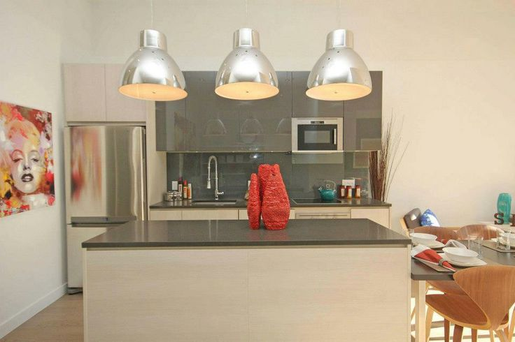 Model condo suite -A kitchen in various shades of grey with some over sized task lighting above the island and some great pops of colour