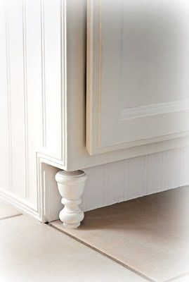 "this is such a great, inexpensive idea to spruce up builder-grade cabinetry. finials instead of expensive ""cabinet feet."" and the beadboard along the toe kick looks really custom as well."
