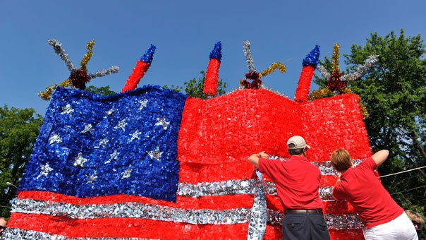 People work on the Cardinal Bank parade float before the start of an Independence Day parade in Fairfax, Va.