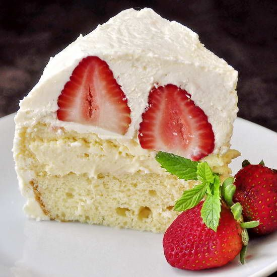 Strawberry Vanilla Buttercream Cheesecake Shortcake, a pound cake bottom gets topped by a whole, crust-less vanilla cheesecake before being crowned with whole ripe strawberries and completely covered in velvety Italian buttercream frosting.