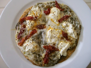 Pizza topped with dollops of ricotta cheese, sun dried tomatoes, pesto ...