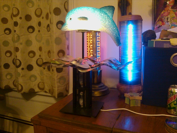 Dolphin light. CD's for the water(heated and bent), base is from a light stand(shade was broke), dolphin part was from a light, to cover the stand and support the CD's I used 8mm tapes.