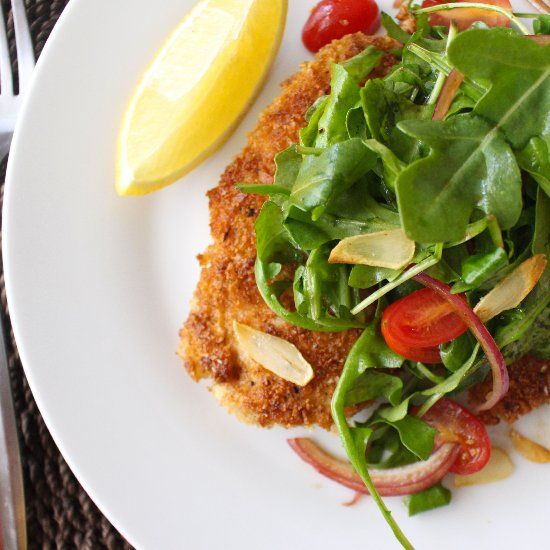Chicken Milanese with arugula salad and fried garlic.