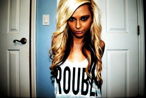 Long blonde hair with black or brown hair underneath in a loose curly ...