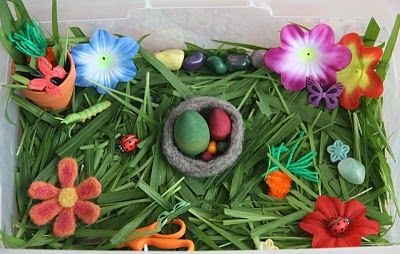 SPRING  Here's what's inside:  :: Real grass (see note below)  :: Mini clay flower pot  :: A needle felted flower  :: Fabric flowers   :: A needle felted nest  :: Wooden eggs  :: Plastic ladybugs, butterflies, and a lone caterpillar  :: Scissors (for cutting the grass   :: Carrots (I made these out of orange pipe cleaners and green yarn)  :: Pretty stones  :: Small ceramic flowers (most of them are buried)