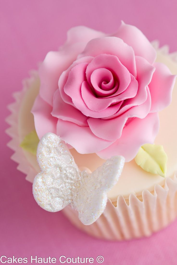 Cupcake decorated with sugar rose and a glitter lace butterfly