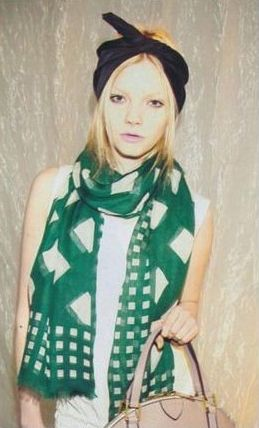... green scarf against plain white tank top, paired with black headband