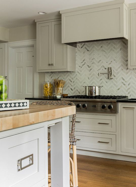 gray cabinetry marble herringbone backsplash butcher block island