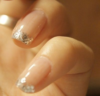 nude nails with silver glitter tips.
