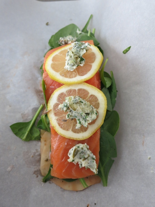 Easter dinner, salmon baked in parchment paper on a bed of sliced ...