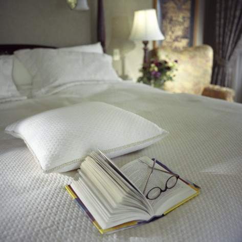A Book with Glasses Left on the Bed Photographic Print