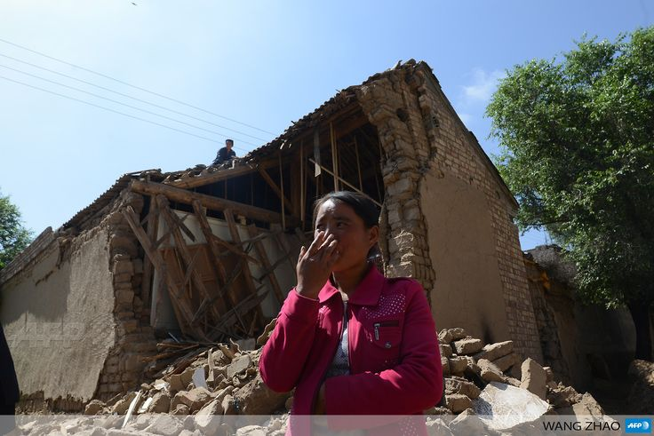 Dingxi China  city photo : CHINA, DINGXI: A local resident stands in front of a house badly ...