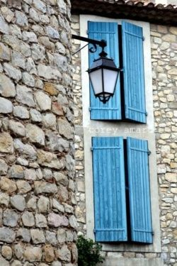 blue shutters in a regular stone wall