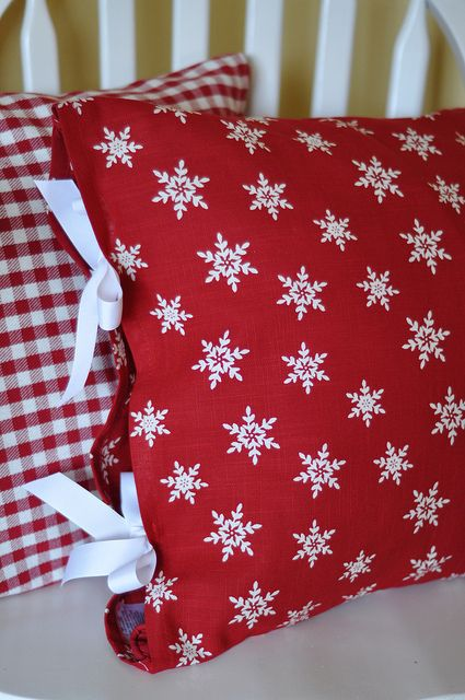 """Make a pillow covers out of 2 colorful; cloth napkins. Makes holiday decorating easy. Sew two sides of napkins together...top and bottom...Then cut 4 lengths of ribbon at 25"""" and then in half, and attached the ribbon to the open ends of the napkin sleeve...Slide the pillow in and tie the ribbon in a bow. Easy peasy!"""