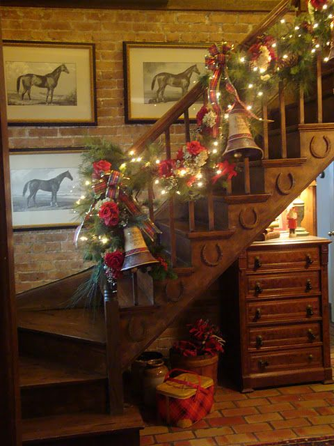 Rustic Decorated Bannister...for the holidays.  Love the horseshoes on the staircase  the bells on the garland.