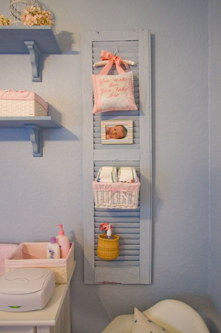 Nursery Storage/Decor: DIY - Amelias Seaside Shabby Chic Nursery (roomzaar.com). Buy old (or new) slatted shutters, power wash them, paint them with the wall color, and dry brush paint a shade darker over the base color.  Add simple white baskets (from Michaels) and a few other accessories and tie each item onto the shutters with ribbon.